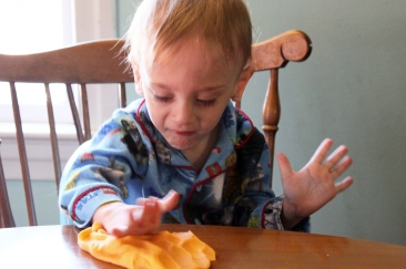 It can be difficult for him to touch the playdough but he tries!